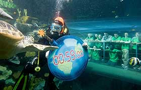 Pictured with naturalist and broadcaster Nick Baker as a diver carries a symbolic 'time-bomb' earth through the ocean tank at the National SEA LIFE Centre, are from left to right: Standing - Tierney Carter, Rebecca Johnson, Amber Rowland (Nick Baker), Ricky Froud, Matthew Newsome and Abigale Rudland. Kneeling - Molly Clayton, Hannah Layton and Kwabe Tenkorang.  Click on this photo to see a larger version >>>