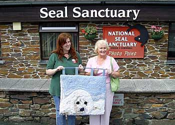 Photo of Rhona presenting Michelle with the rug hook art picture of a seal